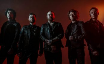 Asking Alexandria band photo. The band all wear leather jackets and are dimly lit against a red wall