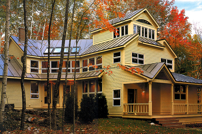 This gorgeous Ontario home features plenty of bright windows, golden siding, and a chestnut steel sheet roof to reflect the colours of autumn around it.