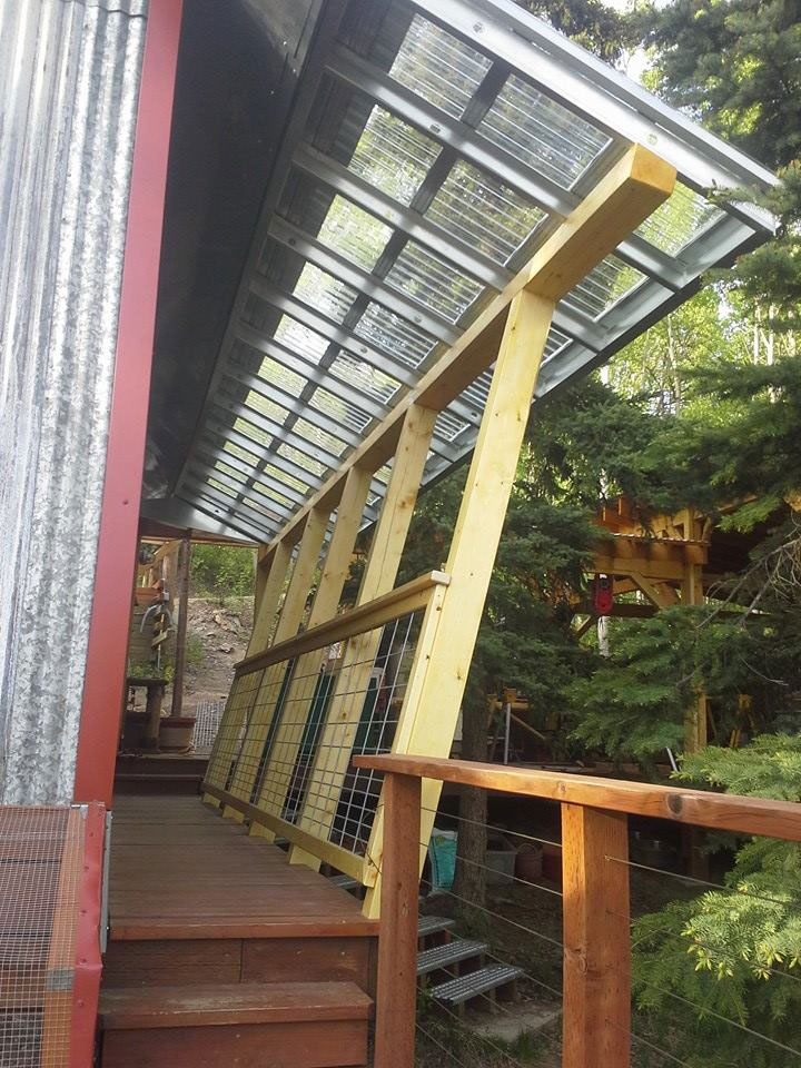 Covered side porch with spruce timbers, galvanized metal rafters and lexan roofing