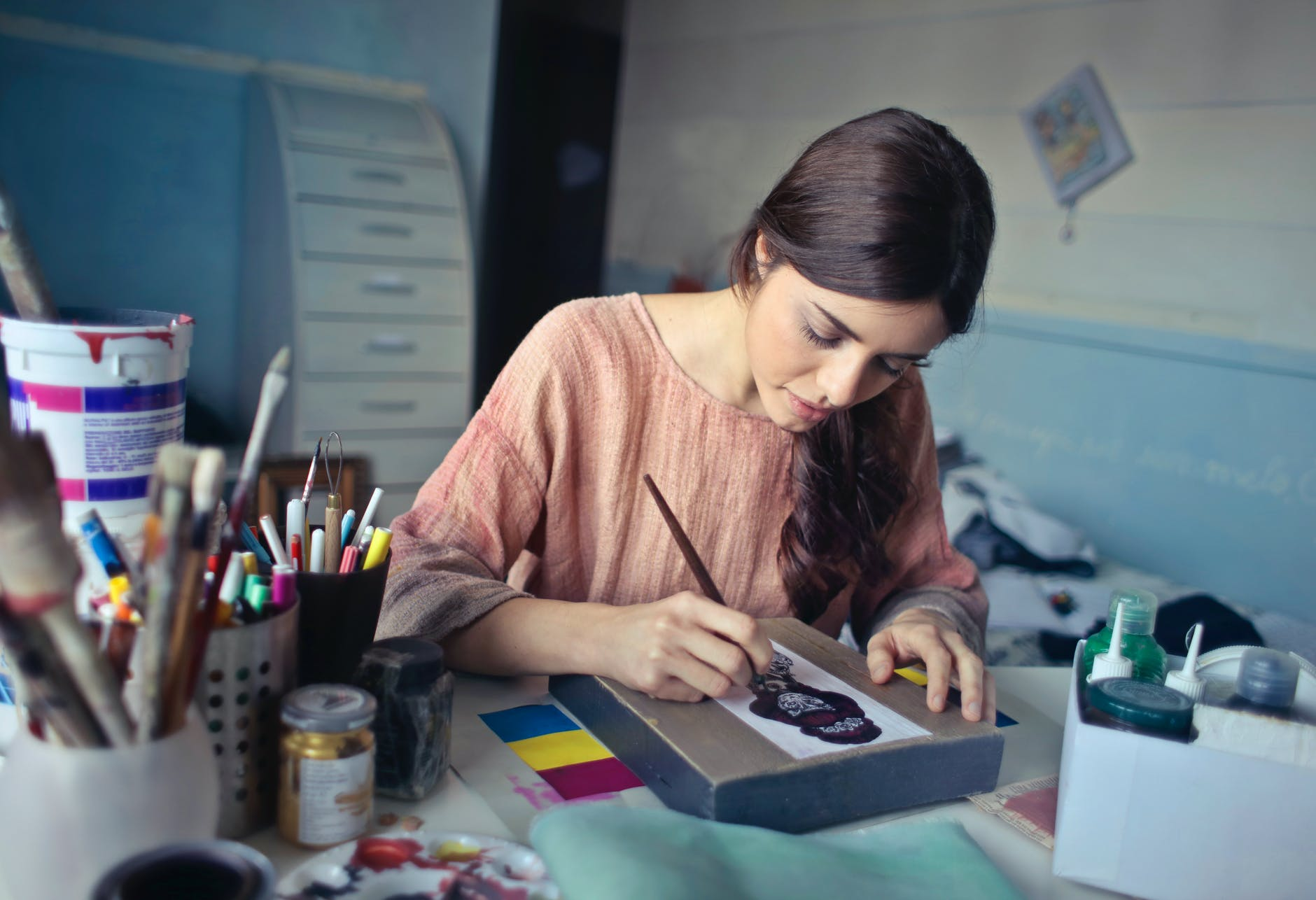 woman in brown scoop neck long sleeved blouse painting