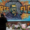 """Ronald Scott, a central neighborhood resident for more than 10 years, takes a photo of the memorial mural over flowers and banners laid in the memory of George Floyd outside of Cup Foods on May 29, 2020, during the fourth day of protests over his death in Minnesota, Minneapolis, United States. Floyd, 46, a black man, was killed Monday when a white officer kneeled on his neck, despite Floyd's repeated pleas of """"I can't breathe."""""""