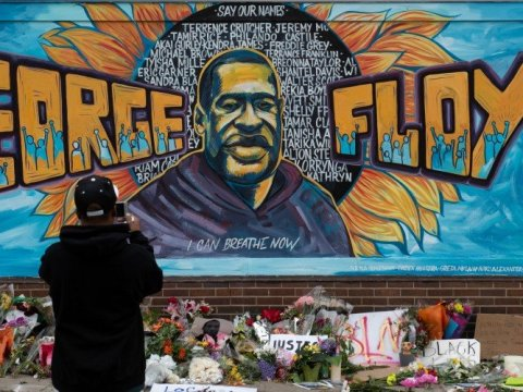 "Ronald Scott, a central neighborhood resident for more than 10 years, takes a photo of the memorial mural over flowers and banners laid in the memory of George Floyd outside of Cup Foods on May 29, 2020, during the fourth day of protests over his death in Minnesota, Minneapolis, United States. Floyd, 46, a black man, was killed Monday when a white officer kneeled on his neck, despite Floyd's repeated pleas of ""I can't breathe."""