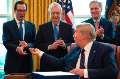 President Donald Trump hands pens to Treasury Secretary Steven Mnuchin, left, and Senate Majority Leader Mitch McConnell, center, after signing the CARES Act on March 27. (Photo: Jim Watson)