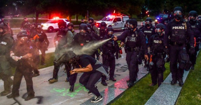 Police officers pepper spray a woman next to the Colorado State Capitol as protests against the killing of George Floyd continue on May 30, 2020 in Denver, Colorado. (Photo: Michael Ciaglo)