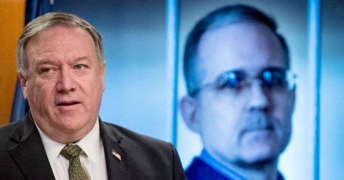 An image of Paul Whelan, a former U.S. marine who was arrested for alleged spying in Moscow, is displayed behind Secretary of State Mike Pompeo as he speaks during a news conference at the State Department in Washington, D.C. on June 10, 2020. (Photo by Andrew Harnik/Pool/ AFP via Getty Images)
