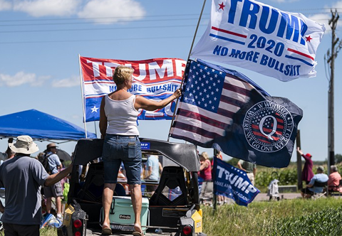 A woman holds a Trump 2020 flag and a QAnon flag outside of Mankato Regional Airport as President Donald Trump makes a campaign stop on August 17, 2020 in Mankato, Minnesota. (Photo: Stephen Maturen/Getty Images)