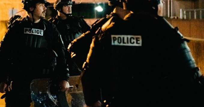 Police officers stand guard inside of a fenced area that surrounds several government buildings on August 27, 2020 in Kenosha, Wisconsin. Wisconsin Gov. Tony Evers approved a request for an additional 500 National Guard troops to be deployed into Wisconsin on August 26. Many arrests have been made with the additional presence of law enforcement.