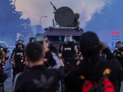 Demonstrators face police armed with military equipment at a recent racial justice protest. (Photo: Amnesty International USA)