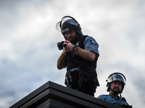 A police officer stands on the roof of the Third Police Precinct in Minneapolis holding a projectile launcher during a demonstration on May 27. (Kerem Yucel/AFP via Getty Images)