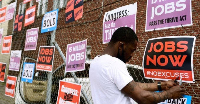 Derrick Davis, a member of West Virginia New Jobs Coalition, hangs up signage during a community gathering and job fair on April 8, 2021 in Charleston, West Virginia. (Photo: Emilee Chinn/Getty Images for Green New Deal Network)