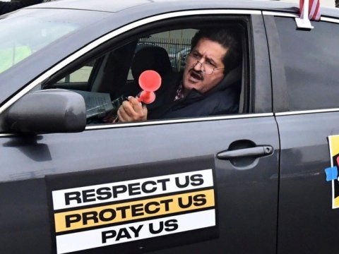 Food delivery driver Jorge Vargas honks a horn while driving his vehicle in a car caravan strike by fast food workers and their supporters on February 9, 2021 in Los Angeles. (Photo: Frederic J. Brown/AFP via Getty Images)