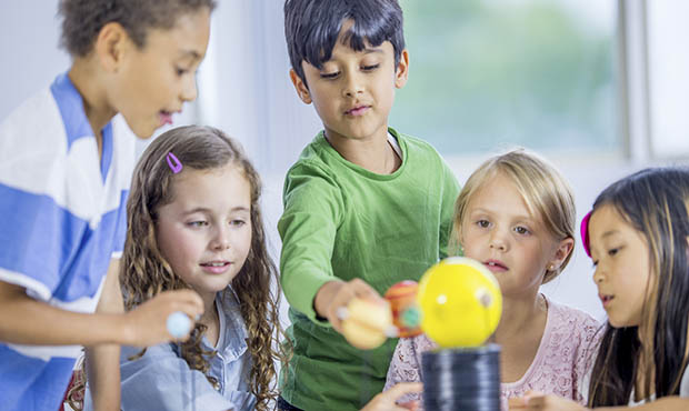 A multi ethnic group of little children sitting at a desk, exploring a model solar system for a science class.