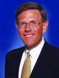 Droegemeier in a suit and tie in front of a dark backdrop