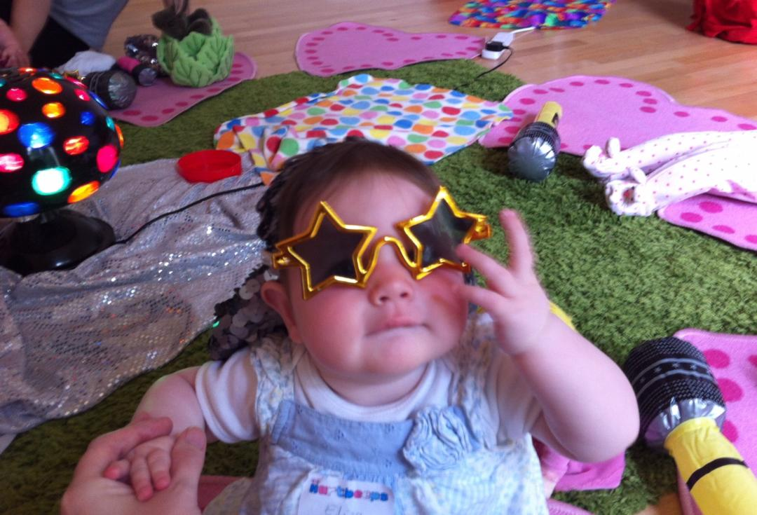 The joys and horrors of baby classes - baby at a class wearing start shaped glasses
