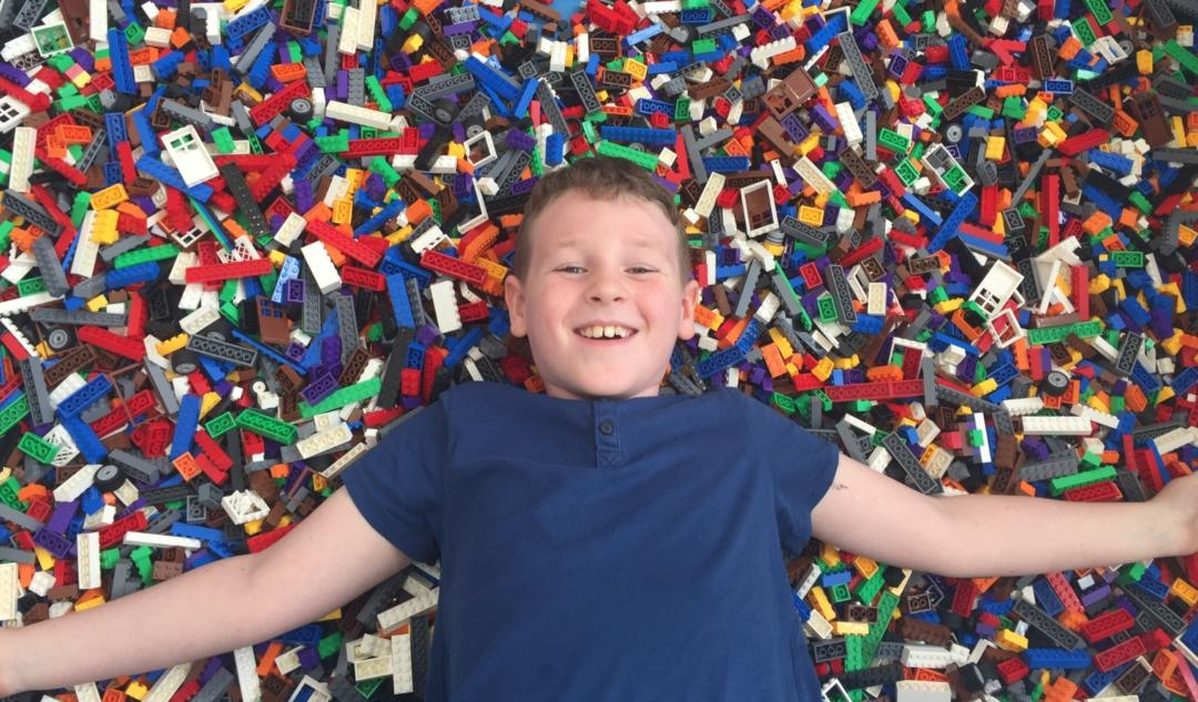 Extrovert child laying in lego