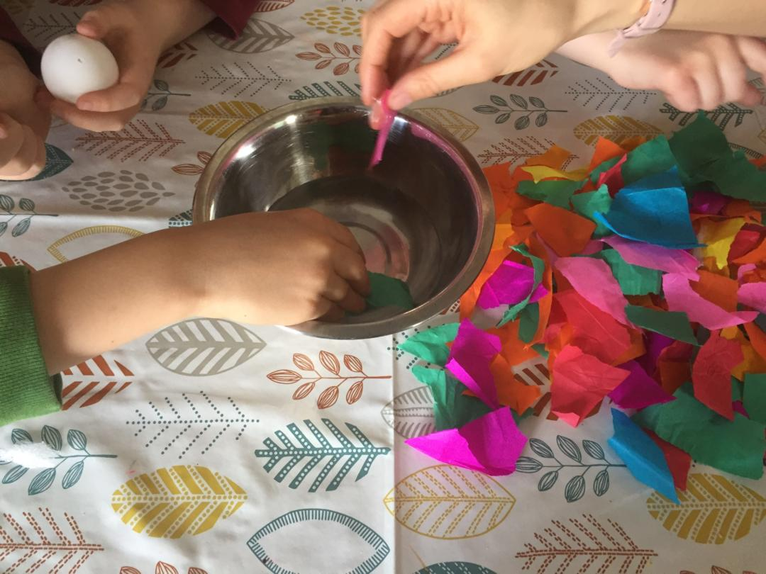 Tissue paper is dipped into the bowl of water and then placed on the egg