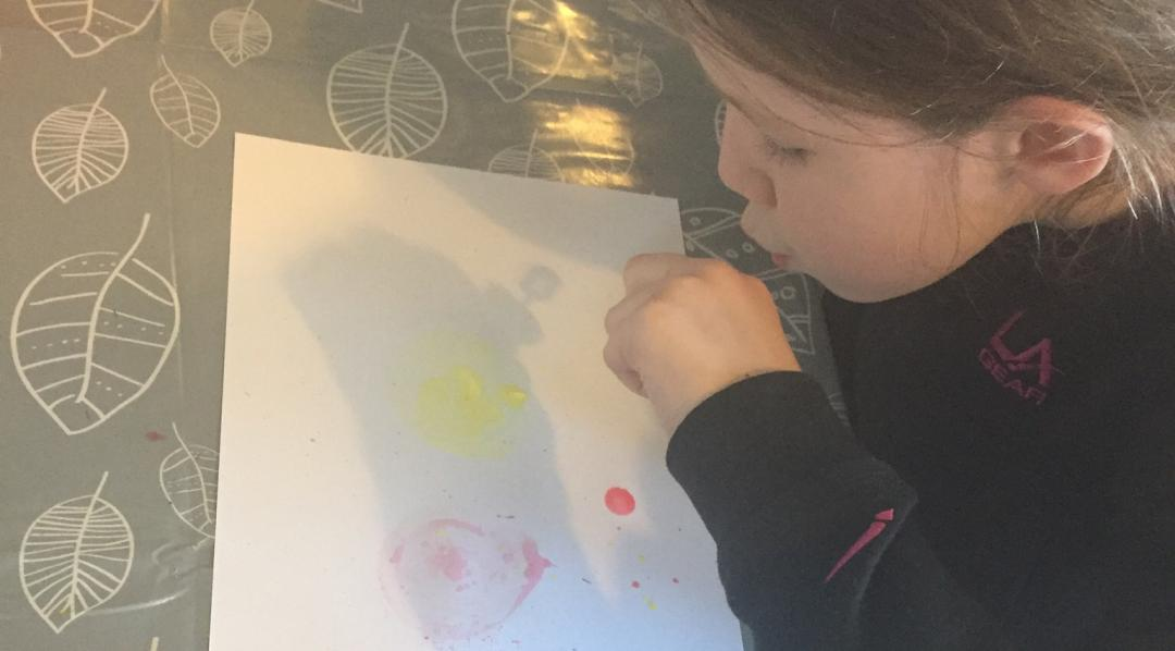 Blowing bubbles onto the paper to create process art