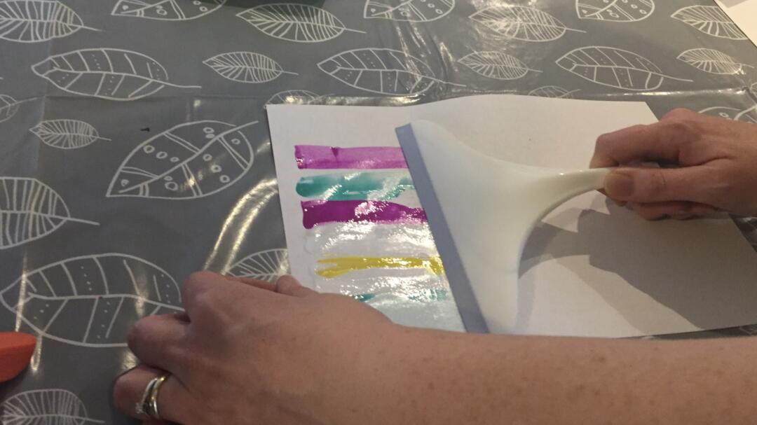Use the squeegee to spread the paint across the paper