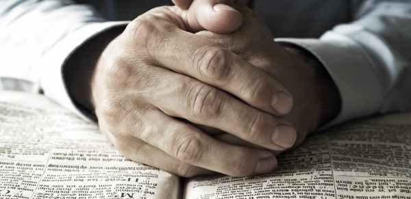 Hands over an open Bible