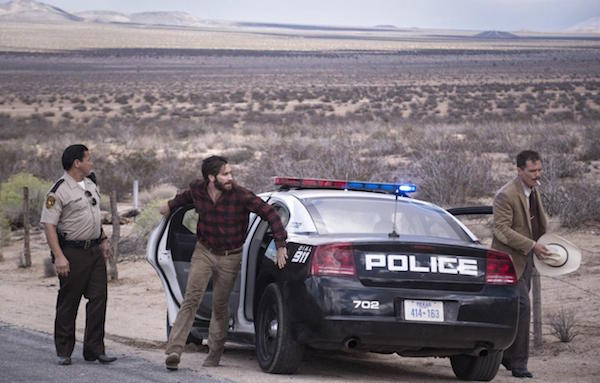 Jake Gyllenhaal and Michael Sheen next to a police car in Nocturnal Animals