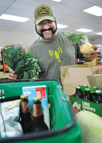 Jeff Lyman rings up  beer, organic milk and fresh, locally grown veggies for a Monday afternoon customer. Photo by Sue Misao