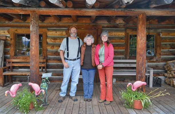 Ron Cramer, left, and camp host Shannon Cramer and Pine Near RV Park co-owner Anna Kominak share the front porch of the park's office building, a log cabin that has been renovated to include coin laundry equipment, showers and restrooms. Photo by Laurelle Walsh