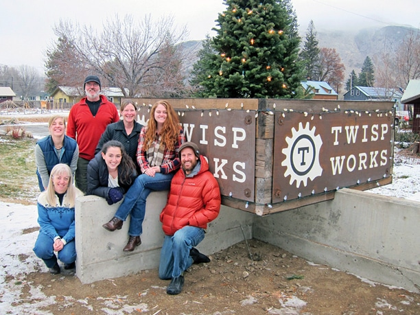 The TwispWorks staff celebrates the organization's new sign, designed and constructed by CorinMcDonald and Brice Butler. Back row, from left: Alison Gilette, Patrick Hannigan and Executive Director Amy Stork. Front row, from left: Anne Acheson, Jill Beckerman, Marissa Burkett and Tori Karpenko. Photo by Don Nelson