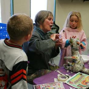Jody Olson, artist-in-residence at Methow Valley Elementary, gives Dashe McCabe, right, some assistance crafting and attaching her raccoon's ears as Lane Darwood looks on. Olson is in her third year of helping local elementary students recreate creatures of the Methow in papier mâché. The animal creations are part of a multi-disciplinary study unit, in which  students also research and report scientific facts about their selected critters in the regular classroom. Photo by Darla Hussey