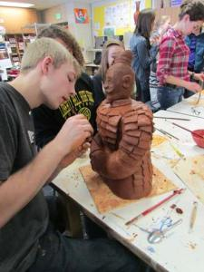 Logan Szafas uses a clay tool to refine the terra cotta warrior he built in collaboration with other ceramics and Chinese students.  Photo by Erin Frey