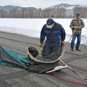 """Pilot Steve Justice does the """"hoop dance"""" that will maneuver the ring  back into a size that will fit inside the carrying bag. Brother Steve Justice, 2nd crew chief, looks on. Photo by Darla Hussey"""