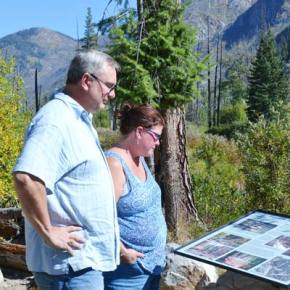 "Brian and Kristen Bruhahn, of Auburn, Washington, read one of the roadside placards that tell the story of the Thirtymile Fire, which erupted on July 9, 2001. ""You can feel a lot of people's pain at the memorial,"" Brian said. Photo by Laurelle Walsh"