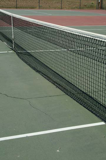 Cracks in the tennis court are a safety hazard. Photo by Marcy Stamper