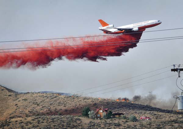 Tanker 911 drops its load of fire retardant on Balky Hill, east of Twisp, on July 18 about 4 p.m.Photo by Sue Misao