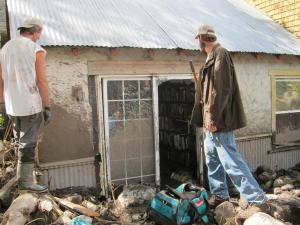 Bob Elk, left, and a helper survey damage to the Elk/Lewis home. Photo by Don Nelson