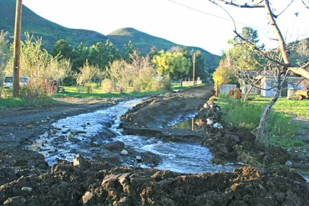 Photo by Marcy StamperWater surged down Frost Road and drained into adjacent fields. A temporary fix engineered by Okanogan County Public Works this week helped divert the water and restore access for residents.