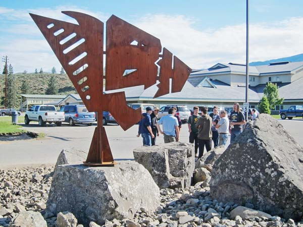 Photo by Don Nelsonthe installed sculpture is at the entrance to the high school parking lot; welding class members are in the background.