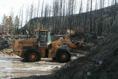 Photo by Marcy StamperHeavy equipment cleared mud, rocks, trees and other debris that cascaded down the west side of Highway 153 at the most serious of three mudslides. Most trees and vegetation in the area burned in wildfires during the past two summers, increasing the risk of erosion.