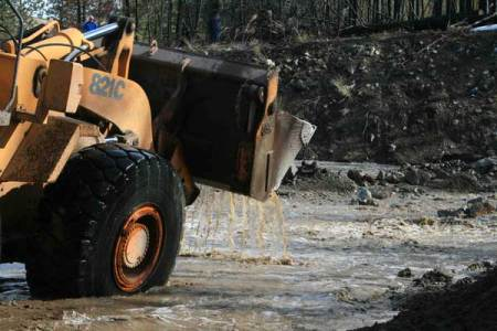 Photo by Marcy StamperA front-end loader scooped mud, rocks, tree roots and other debris to divert the flow.