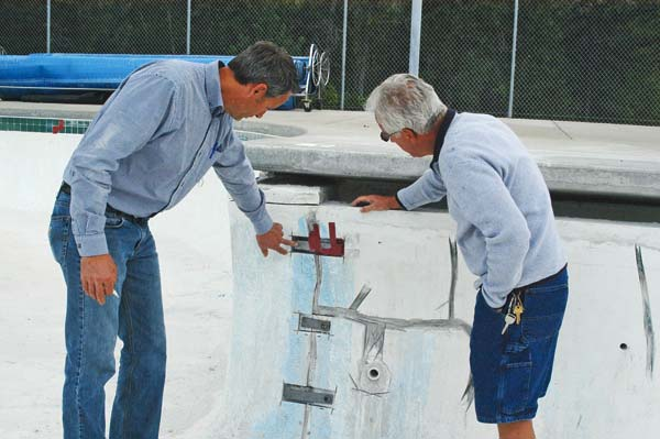 "Photo by Ann McCreary Twisp Public Works Director Andrew Denham, left, shows Twisp Town Council member Alan Caswell one of the many cracks in the Wagner Memorial Pool that have been ""stapled"" together with metal joints to prevent them from growing."