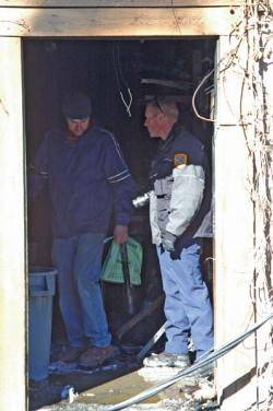 Photo by Ann McCreary Pub owner Aaron Studen, left, talked with fire investigator Brian Brett on Monday.