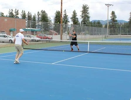 Photo by Don Nelson Liberty Bell High School tennis coach Dave Schulz, left, tries out the new courts that were resurfaced this week.