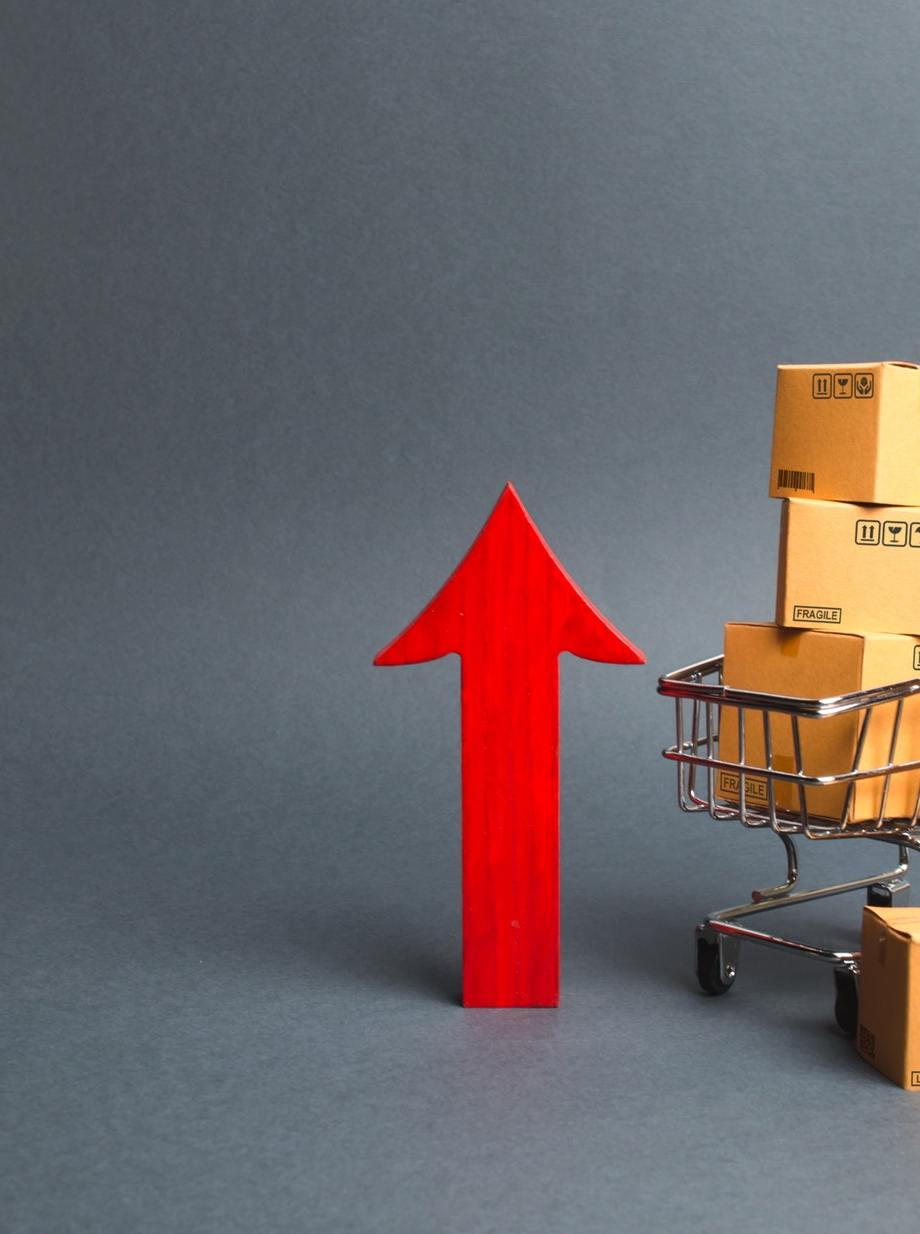 Shopping cart with cardboard boxes and red up arrow