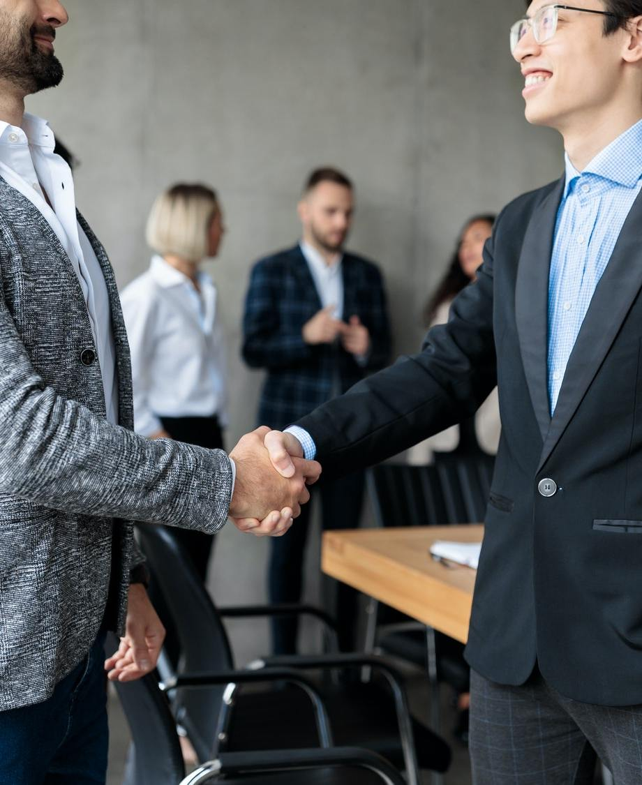 Two Businessmen Shaking Hands After Successful Negotiations In Office