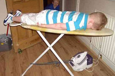 This boy  on an ironing board is a fine example of the lying down game