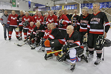 A group of hockey players, all 80 years old and over, pose for shots after their game
