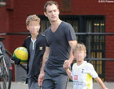 Actor Jude Law takes a walk with his sons Rafferty and Rudy in the West Village after playing football