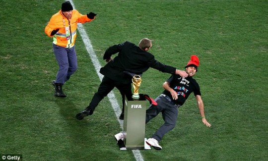 Notorious pitch invader Jimmy Jump is wrestled away from the World Cup trophy