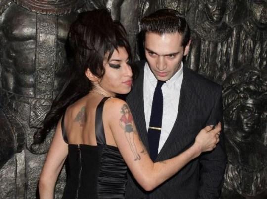 Amy Winehouse keeps close to boyfriend Reg Traviss (Photo: PA)