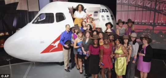 Oprah Winfrey, top, stands with audience members after making the announcement she will be taking the studio audience on a trip to Australia