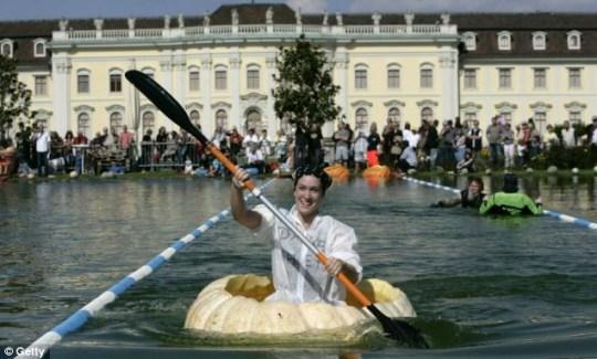 Inge Schrimps paddles her hollow pumpkin across Ludwigsburg Castle lake on Sunday
